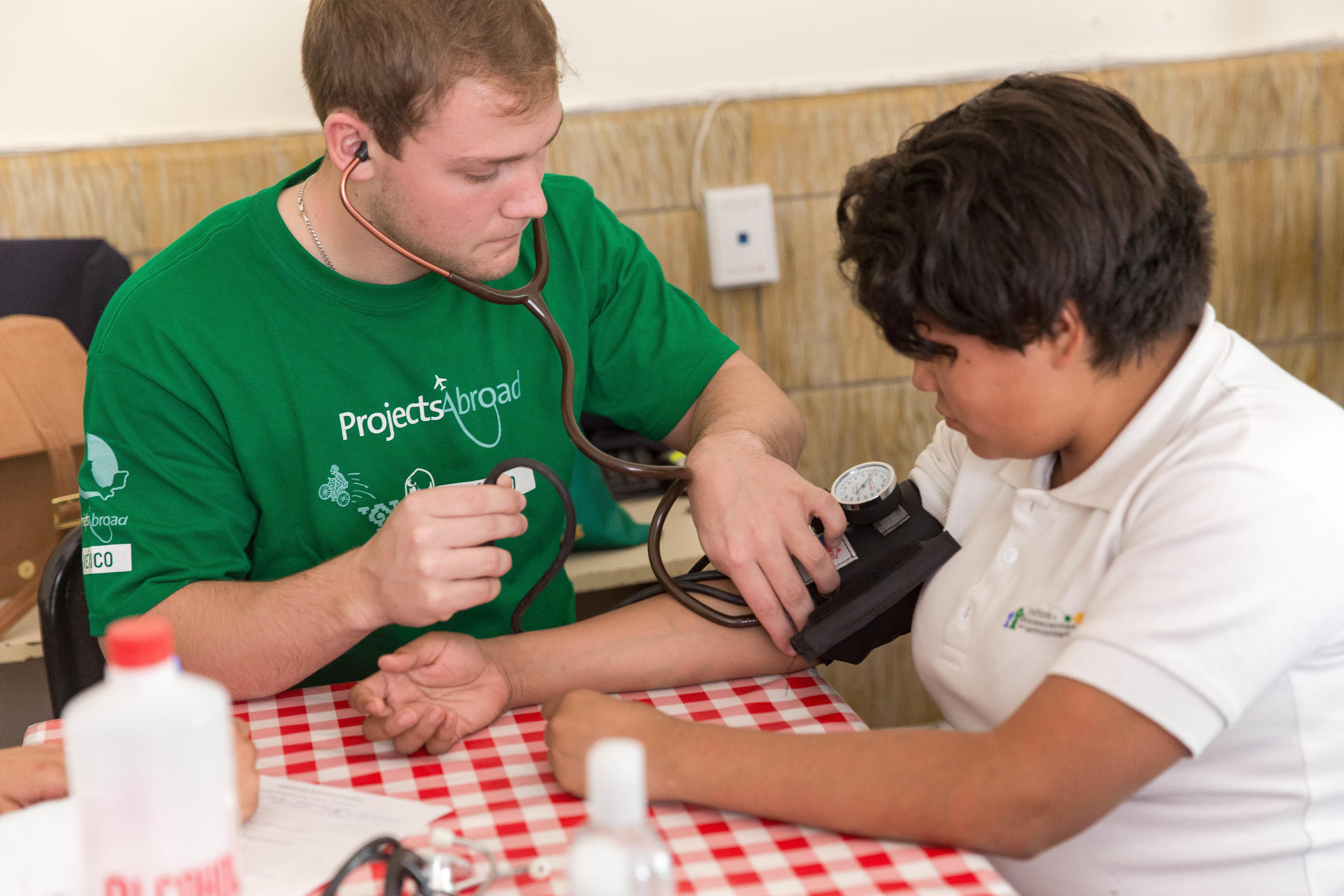 A male Projects Abroad intern is pictured taking the blood pressure of a local patient as part of his nursing internship in Mexico.